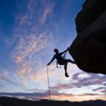 A rock climber is silhouetted against the evening sky as he rappels past an overhang in Joshua Tree National Park.