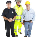 Group of blue collar workers isolated on white, including a firefighter, police officer, and construction worker.